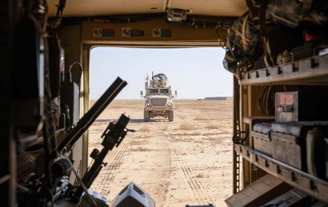 U.S. troops stationed at Al Asad Air Base in Iraq drive trucks on their way to conduct training exercises.