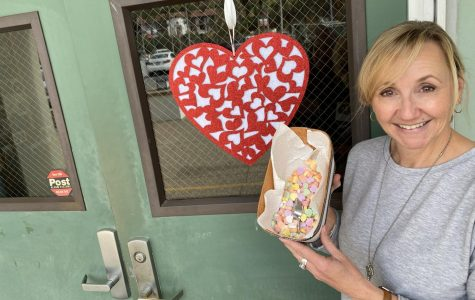 Attendance clerk, Ms. Audra Ward, shows off her box of Sweetheart candies, an iconic staple of Valentine's Day.