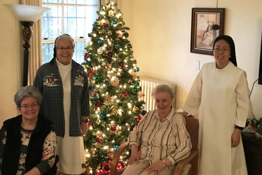 Sister Elizabeth, Sister Celeste, Sister Katherine Jean and Sister Mary (from left to right) pose in front of the tree in their community room. Sister Celeste's favorite ornaments were made out of straw by a sister in Germany.