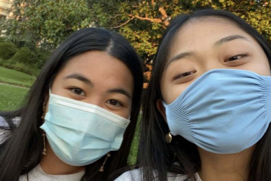 Katrina Manaloto '20 (left) and Meg Kalaw '20 (right) do their online classes together outside, on the Berkeley campus, with masks.