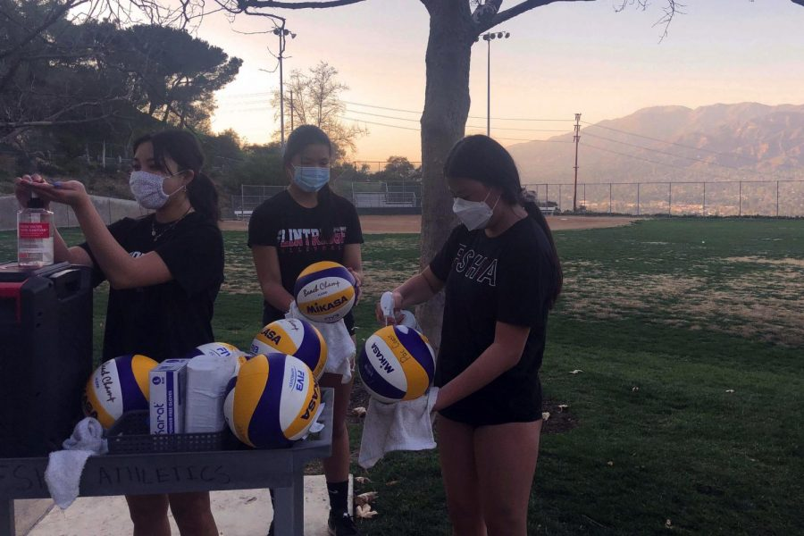 Volleyball players (from left to right, Angelina Cao '22, Isabella Cao '22 and Sara Park '22) clean off the volleyballs after their practice on Crane Field.
