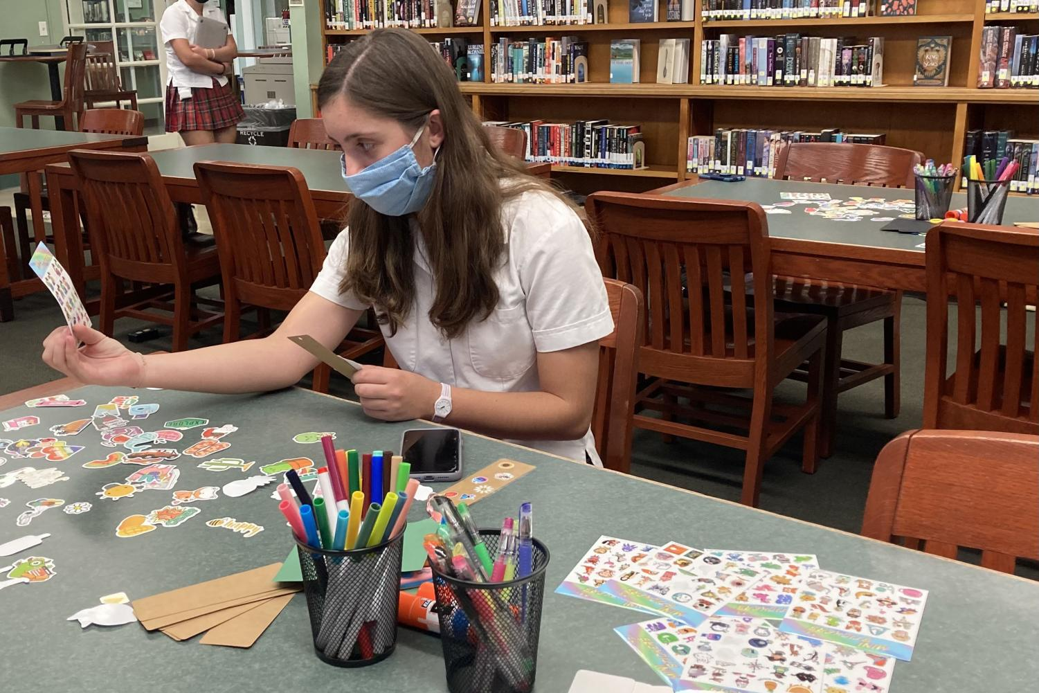 Adele Kelley '22 ponders the stickers at a bookmark-making event hosted by the school library.
